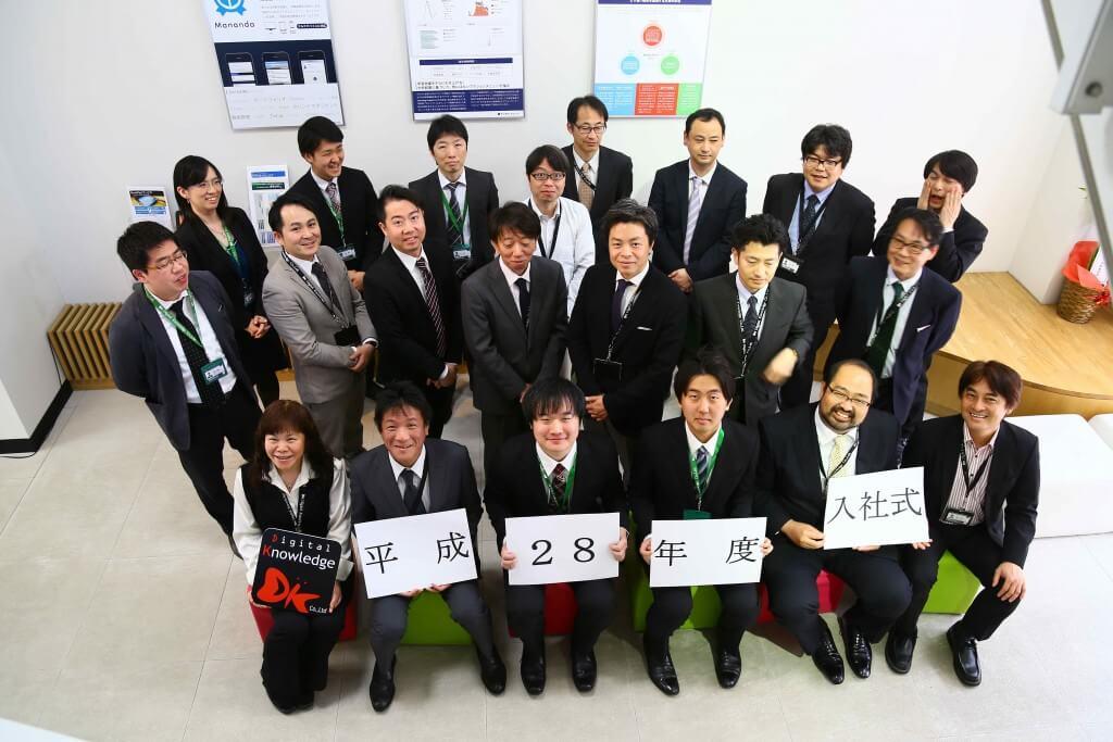 平成28年度入社式での2名の新入社員と役員・チュータたちとの集合写真
