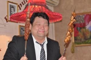 グルジア料理である串焼きを楽しむ社員