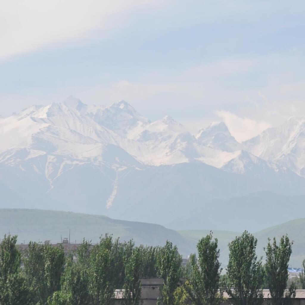 5階建ビルの最上階オフィスから見える晴れた日の天山山脈