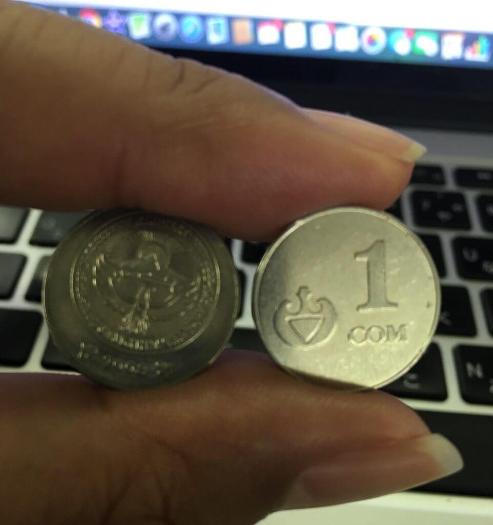 指で挟んだ2枚のキルギスの硬貨1COM